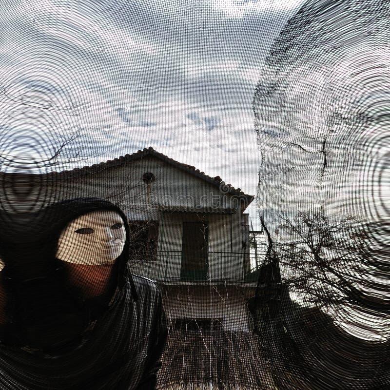 Figura malvada enmascarada detrás de la ventana roscada imagenes de archivo