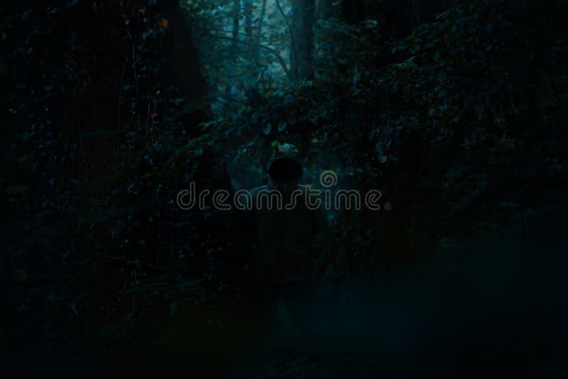 Figura masculina escura assustador em uma posição do hoodie entre árvores com a luz misteriosa que vem atrás dele, cena do horror fotos de stock