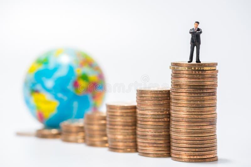 Figura miniatura del negocio que se coloca en la pila de las monedas y del globo f fotografía de archivo libre de regalías