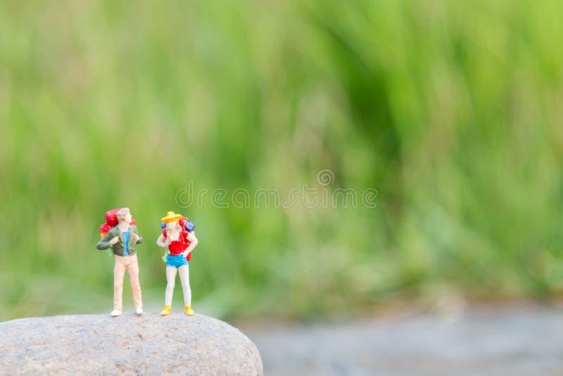 Figura miniatura del viaggiatore mini con il supporto dello zaino e la o di camminata fotografia stock libera da diritti