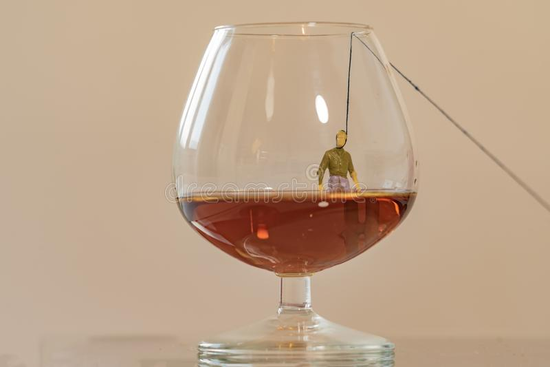 Figura miniatura dell'uomo che appende nel vetro di brandy Fondo basso di profondità di campo Concetto di alcolismo e di sanità fotografia stock