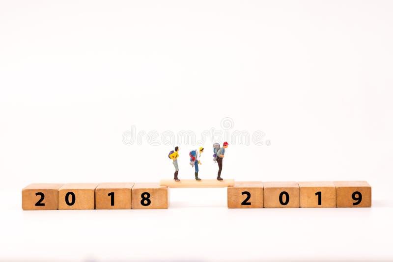 figura miniatura della gente con lo zaino che cammina sul blocchetto di legno di numero fotografie stock