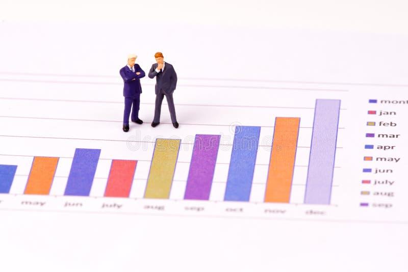 Figura miniatura hombres de negocios que miran la carta del gráfico de barra imágenes de archivo libres de regalías