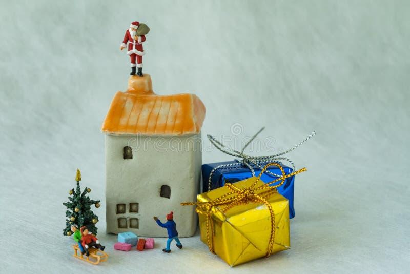 Figura miniatura il Babbo Natale che sta sul camino e sul childr del tetto immagini stock