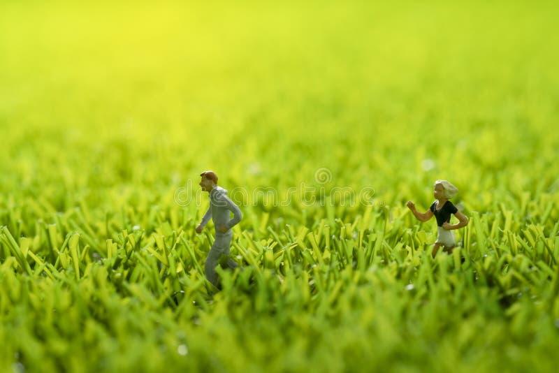 Figura miniatura la gente che corre su erba verde fotografie stock libere da diritti