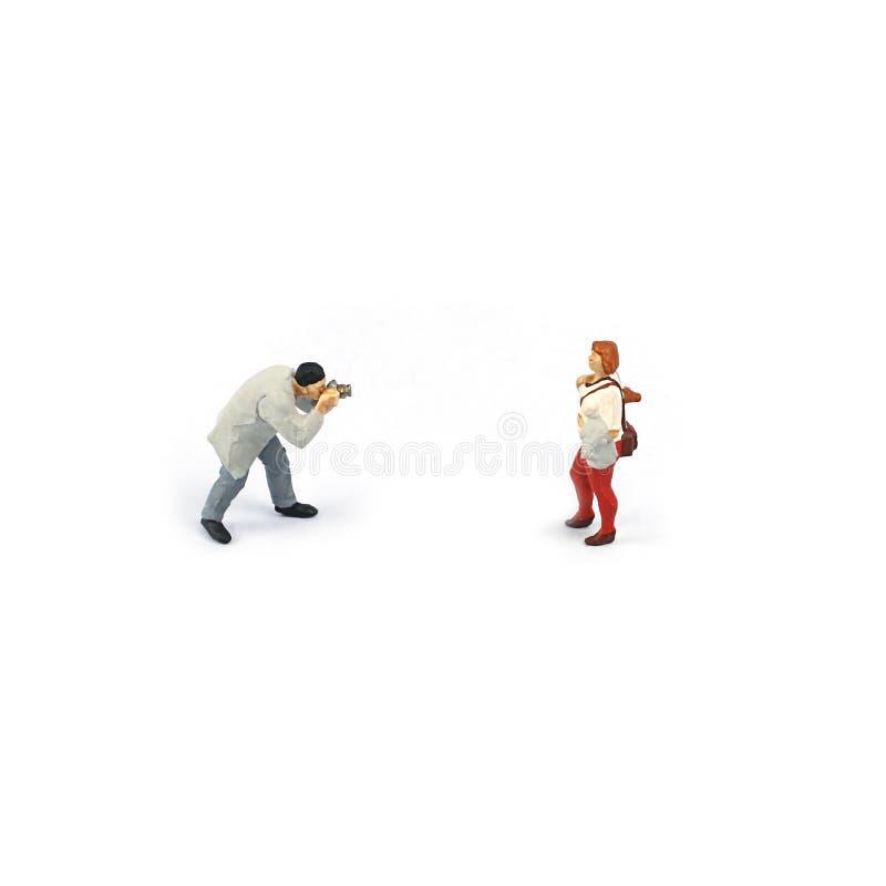 Figura miniatura la gente, fotografo per prendere una foto per la ragazza immagini stock libere da diritti