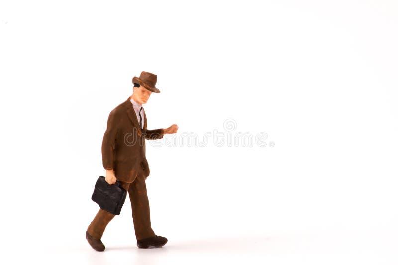 Figura miniatura passeggiata dell'uomo d'affari su fondo bianco fotografia stock libera da diritti