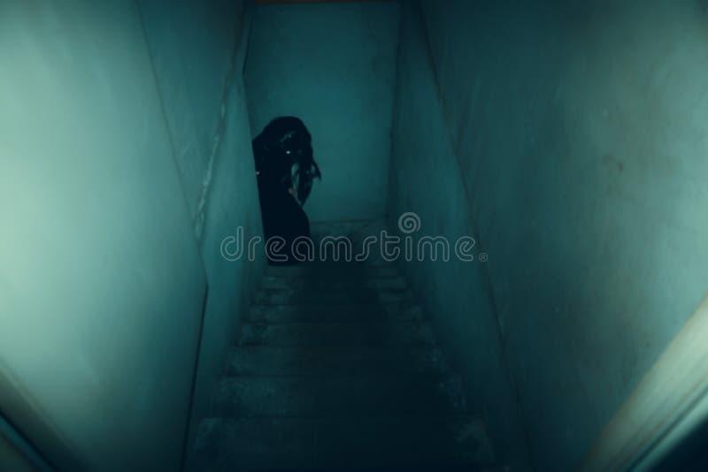 Figura oscura en las escaleras concretas viejas en la pendiente al sótano foto de archivo