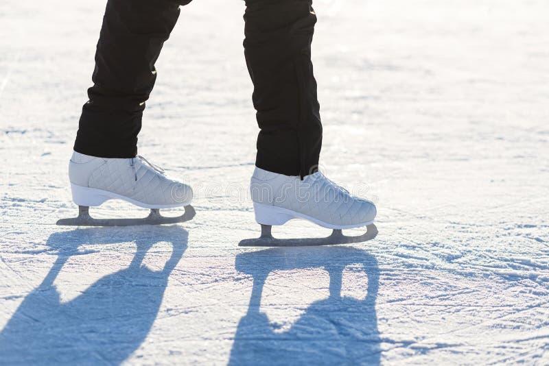 Figura patines del hielo en el primer de las piernas de la mujer imagenes de archivo
