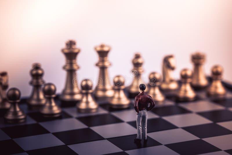 Figura pequena homem de negócios dos povos diminutos que está apenas no jogo de mesa da xadrez fotos de stock