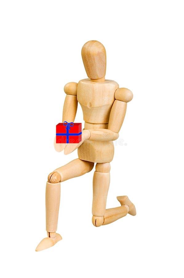 A figura ser humano de madeira da estatueta do homem faz a mostras a ação emocional em um fundo branco No amor com uma caixa de p fotografia de stock