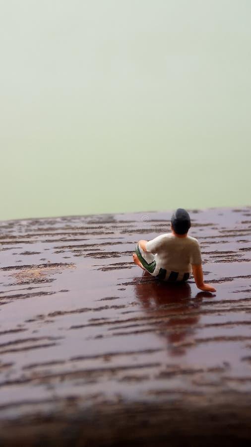 Figura simple, mini viejo hombre del juguete sentarse en el balcón de madera del rasguño en el lado del río con la copia o espaci imagen de archivo libre de regalías