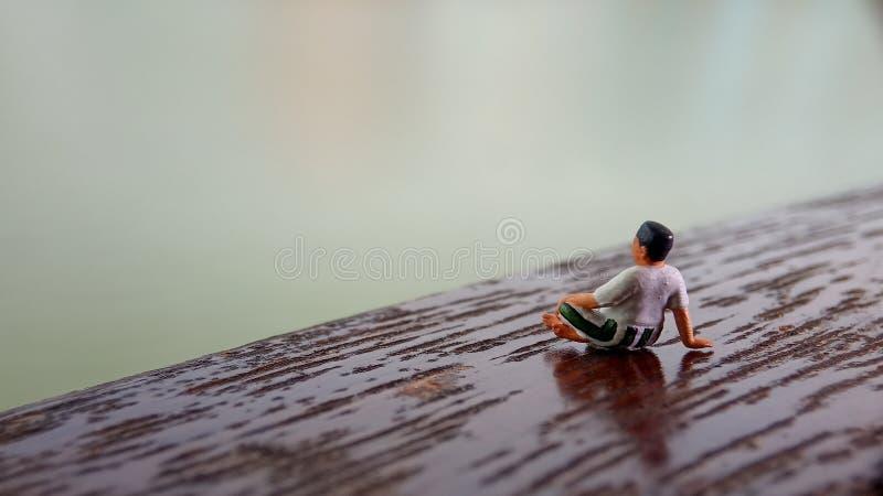 Figura simple, mini viejo hombre del juguete sentarse en el balcón de madera del rasguño en el lado del río con la copia o espaci foto de archivo libre de regalías