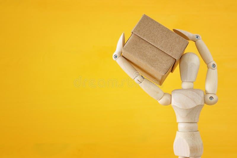 figura simulada de madera que sostiene la actual caja sobre fondo amarillo foto de archivo