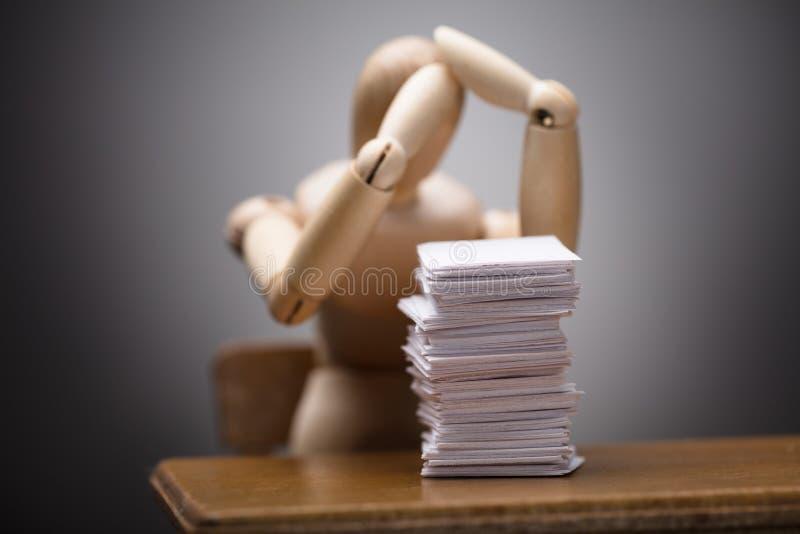 Figura simulada de madera que sufre del dolor de cabeza que se sienta en silla imagen de archivo