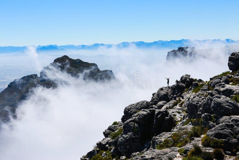 Figura solitaria actitudes encima de la montaña de la tabla imagen de archivo