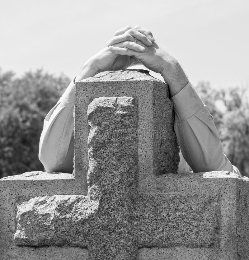 Figura solitaria de la persona en afligirse blanco y negro en el cementerio fotos de archivo