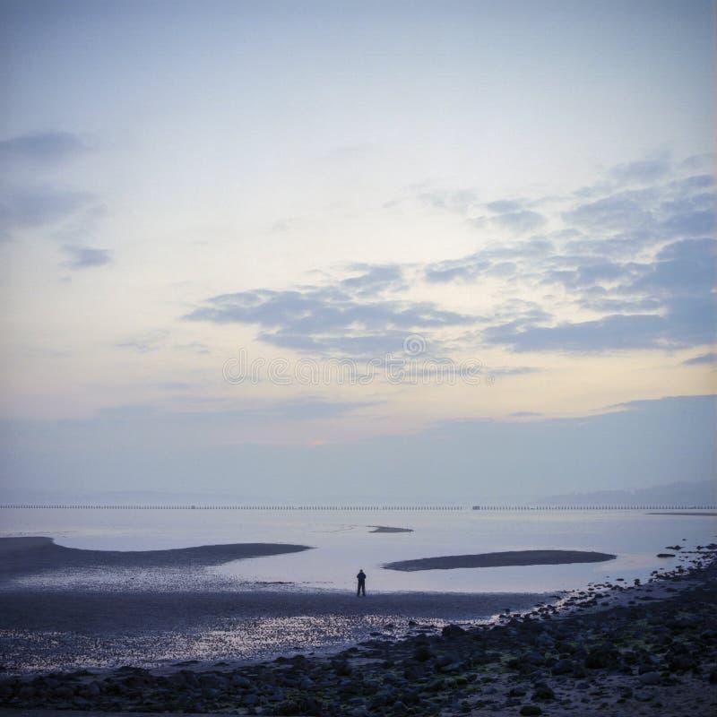 Figura solitaria en una playa fotos de archivo libres de regalías