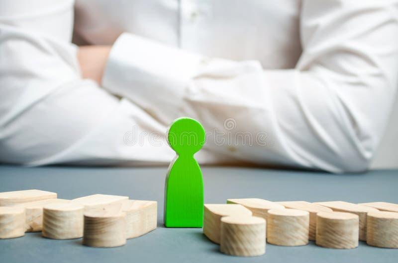 A figura verde de um homem está entre os povos de encontro Escolha bem sucedida O líder escolhe a pessoa o na equipe imagem de stock royalty free
