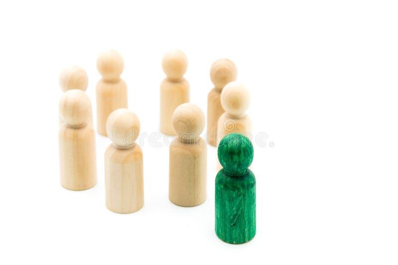 Figura verde que se coloca hacia fuera de la muchedumbre delante del círculo de figuras de madera, aislado en el fondo blanco foto de archivo