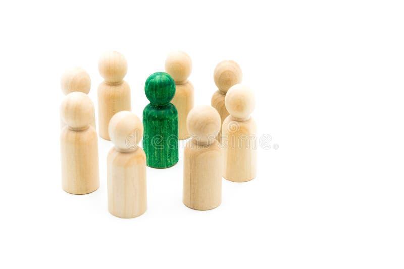 Figura verde que se coloca hacia fuera de la muchedumbre dentro del círculo de figuras de madera, aislado en el fondo blanco fotografía de archivo