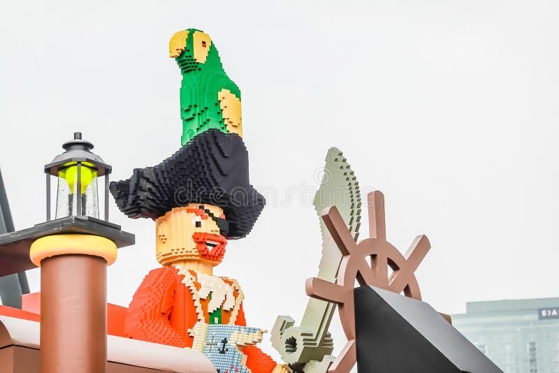 Figuras bandera del capitán del juguete de Lego y del cráneo del pirata en la nave, estilo náutico del viaje, colección plástica  imagen de archivo