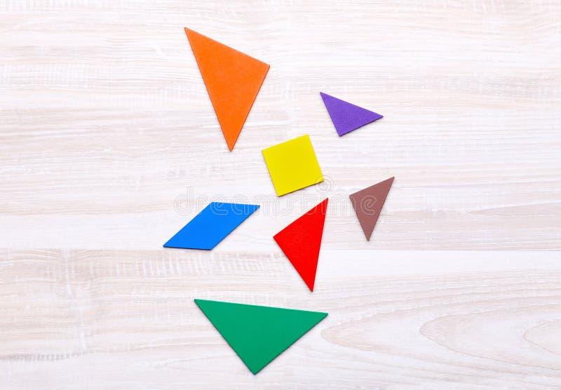Figuras brilhantes do enigma em um fundo de madeira fotografia de stock