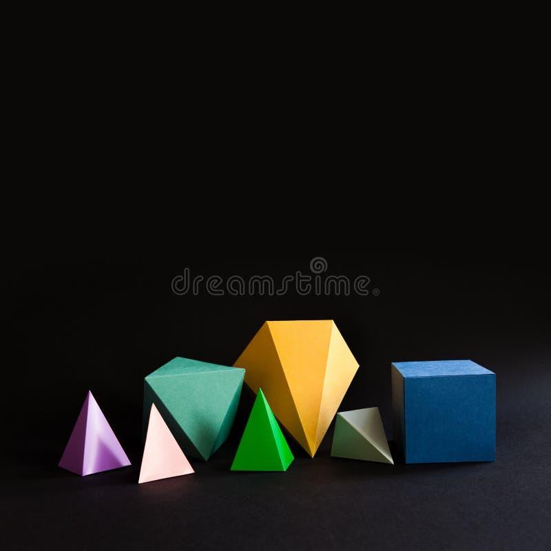 Figuras contínuas geométricas do sumário minimalistic colorido da composição no fundo preto Cubo retangular de prisma da pirâmide imagem de stock royalty free