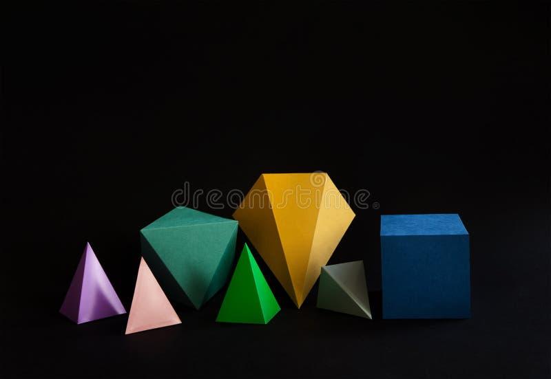 Figuras contínuas geométricas do sumário minimalistic colorido da composição no fundo preto Cubo retangular de prisma da pirâmide fotografia de stock royalty free