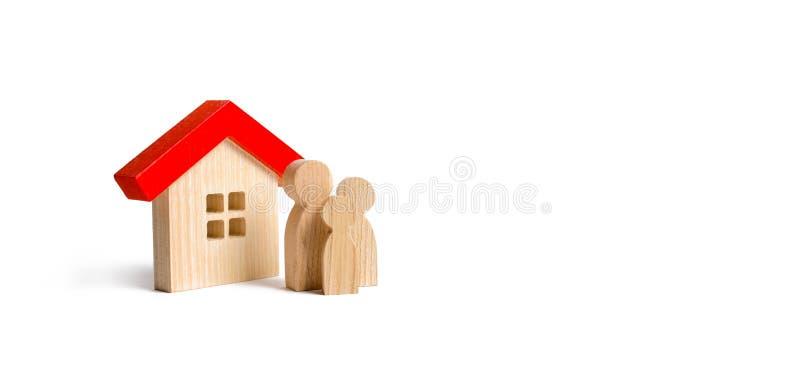 Figuras da família e da casa em um fundo isolado bens imobiliários, sua própria casa Alojamento disponível no crédito ou na hipot fotografia de stock royalty free