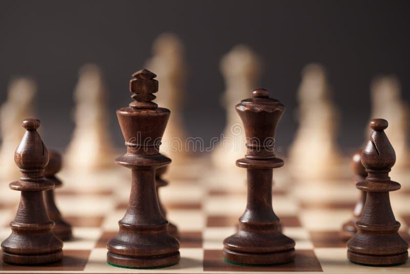 Figuras da xadrez na placa de xadrez foto de stock