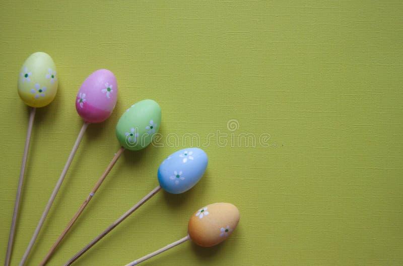 Figuras de la decoración de los huevos de Pascua en fondo verde Contexto de Pascua imagenes de archivo