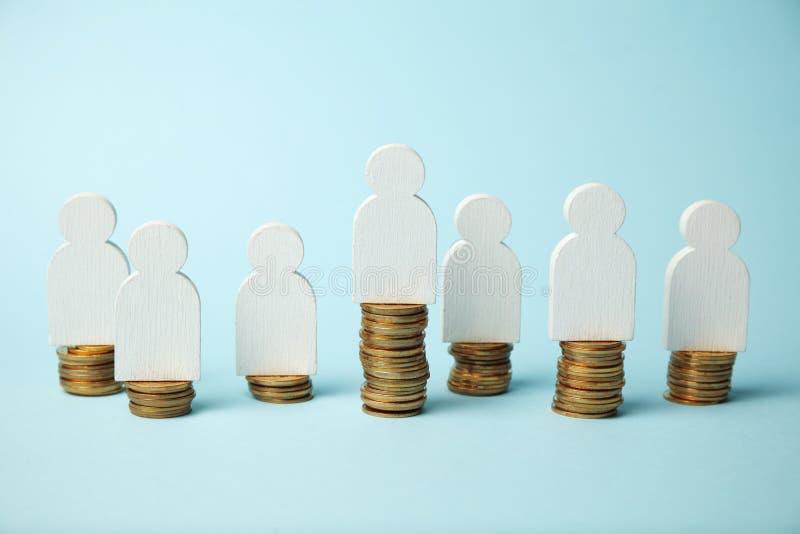 Figuras de la gente en pilas de monedas Diversos niveles de las ganancias de la gente, crecimiento de la pensi?n foto de archivo