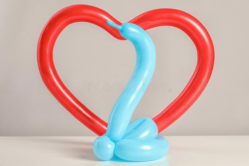 Figuras de la serpiente y del corazón hechas de modelar los globos en la tabla foto de archivo