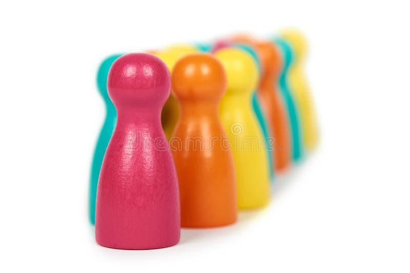 Figuras de madeira do jogo do lazer do penhor Isolado no fundo branco, ideia social, problema dos imigrantes togetherness fotografia de stock