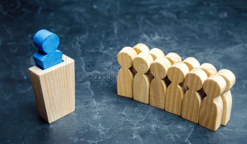 Figuras de madeira dos povos O chefe da equipe do negócio indica o sentido de movimento ao objetivo A multidão está seguindo imagens de stock