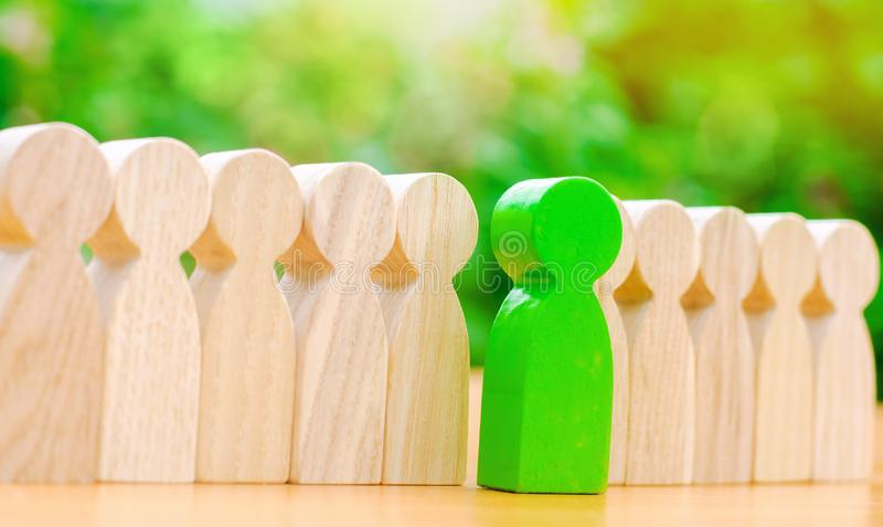 Figuras de madeira dos povos O homem verde sai com uma equipe dos trabalhadores O conceito de escolher um líder novo Escolha da p fotografia de stock