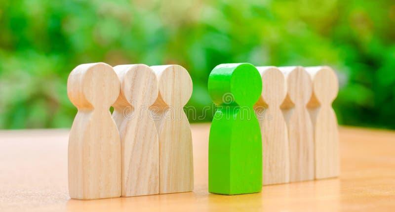 Figuras de madeira dos povos O homem verde sai com uma equipe dos trabalhadores O conceito de escolher um líder novo Escolha da p imagens de stock royalty free