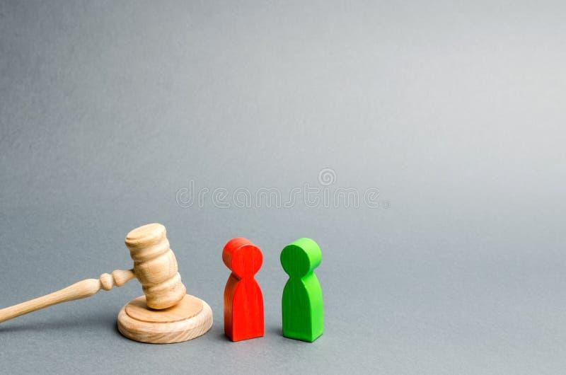 Figuras de madeira dos povos que est?o perto do martelo do juiz litigation Rivais de neg?cio Lei e justi?a do conflito de interes imagem de stock