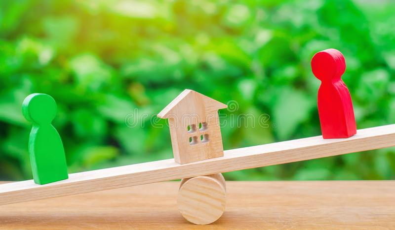 Figuras de madeira nas escalas esclarecimento da posse da casa, bens imobiliários rivais no negócio competição, corte propriedade foto de stock royalty free