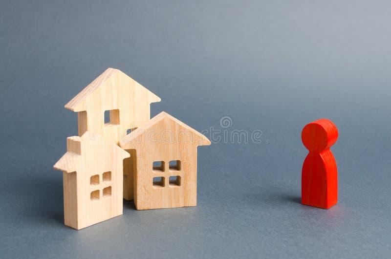 Figuras de madera de casas y una figura roja de la persona en un fondo gris Adquisición de las propiedades inmobiliarias y de los fotos de archivo