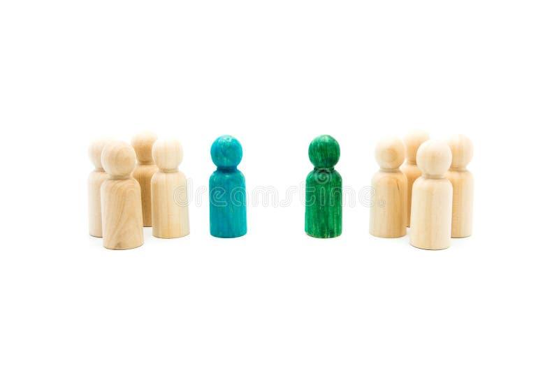 Figuras de madera en línea como equipo del negocio, con las figuras azules y verdes colocándose hacia fuera de la muchedumbre, ai imagen de archivo