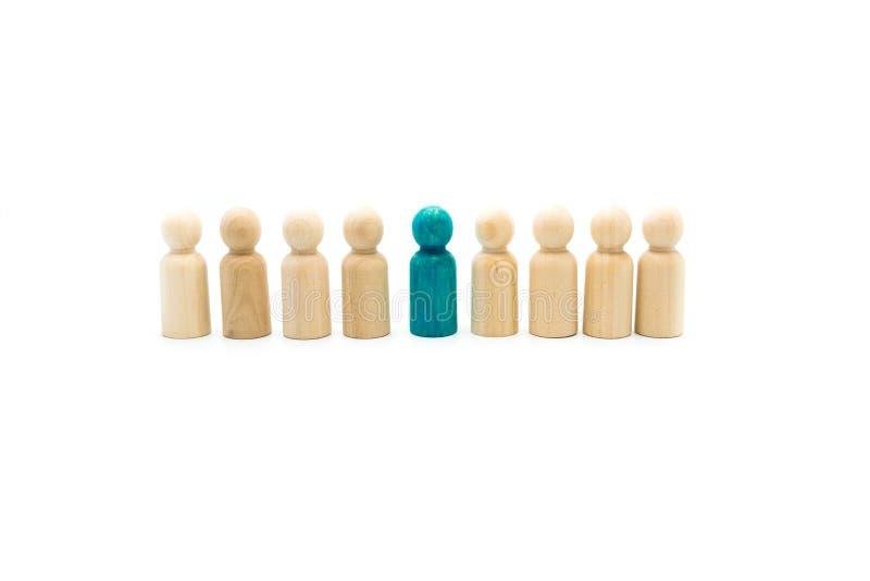 Figuras de madera en línea como equipo del negocio, con una figura azul colocándose hacia fuera de la muchedumbre, aislada en el  imagen de archivo