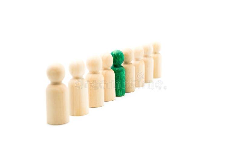 Figuras de madera en línea como equipo del negocio, con una figura verde colocándose hacia fuera de la muchedumbre, aislada en el fotos de archivo libres de regalías
