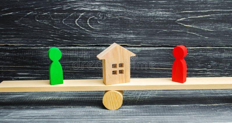 Figuras de madera en las escalas clarificación de la propiedad de la casa, propiedades inmobiliarias corte rivales en negocio com fotografía de archivo