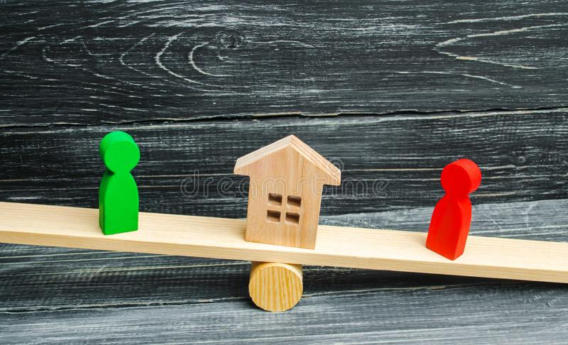 Figuras de madera en las escalas clarificación de la propiedad de la casa, propiedades inmobiliarias corte rivales en negocio com imagenes de archivo