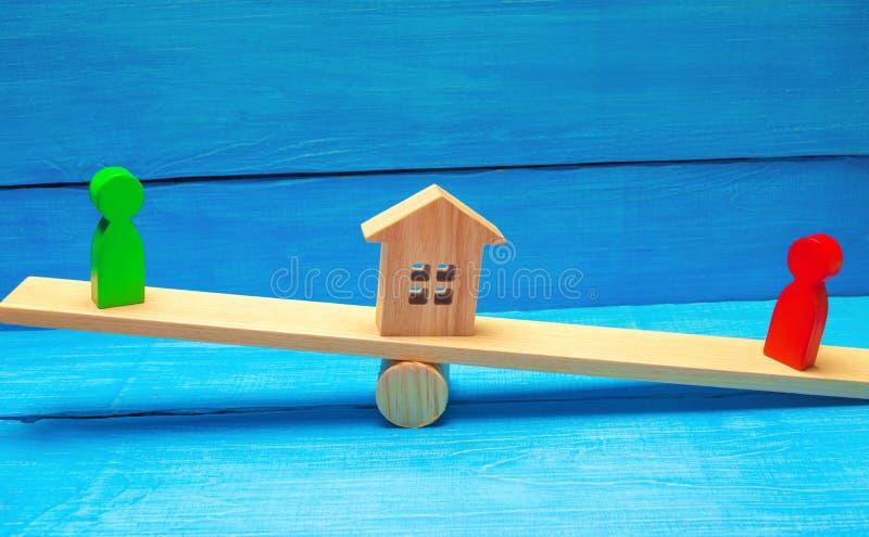 Figuras de madera en las escalas clarificación de la propiedad de la casa, propiedades inmobiliarias corte rivales en negocio com foto de archivo