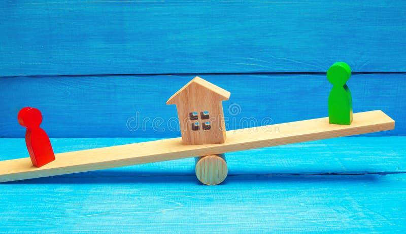 Figuras de madera en las escalas clarificación de la propiedad de la casa, propiedades inmobiliarias corte rivales en negocio com imagen de archivo