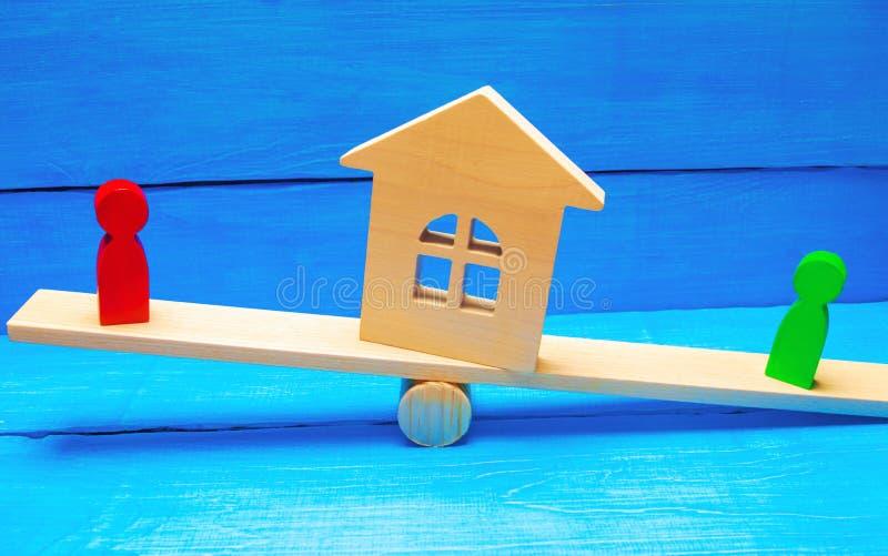 Figuras de madera en las escalas clarificación de la propiedad de la casa, propiedades inmobiliarias corte rivales en negocio com imágenes de archivo libres de regalías