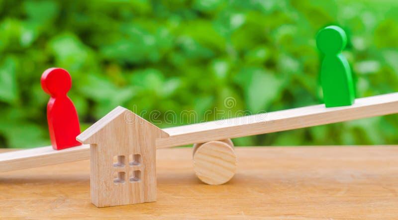 Figuras de madera en las escalas clarificación de la propiedad de la casa, propiedades inmobiliarias rivales en negocio competenc fotografía de archivo